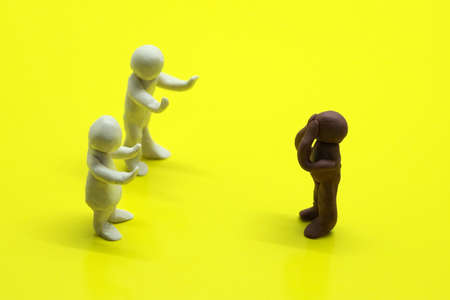 plasticine figures of people on a yellow background, showing problems in relationships, racism, misunderstanding between people