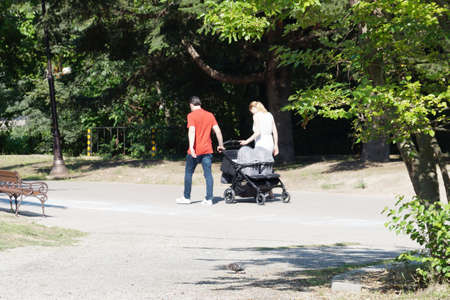 young couple walks in the park with twins in a stroller