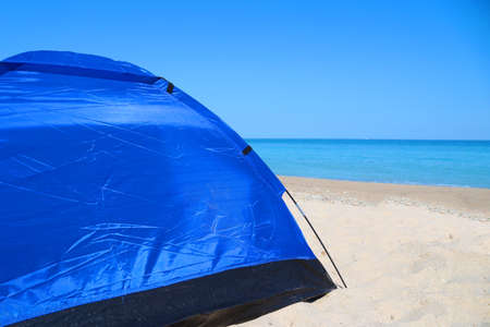 blue tourist tent on the sand against the sea, copy space
