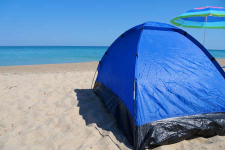 blue tourist tent and beach umbrella on an empty sea sandy shore against a clear horizon, copy space 스톡 콘텐츠