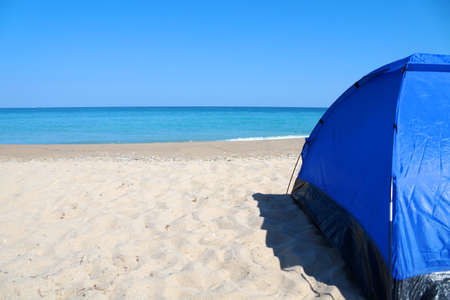 blue tourist tent on an empty sandy beach by the sea, copy space 스톡 콘텐츠