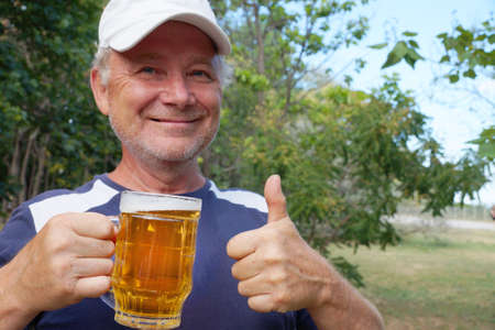 a laughing man holds a mug of beer in one hand, with the other hand shows that everything is fine in the park Zdjęcie Seryjne