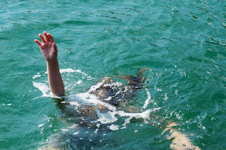 drowning girl raised her hand above the water