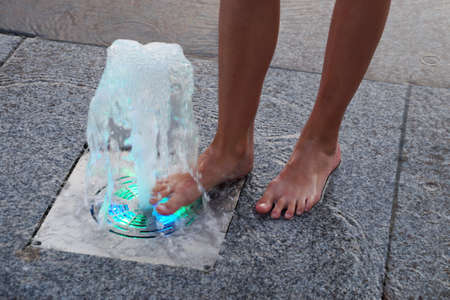 feet of a girl near a colored fountain on the sidewalk