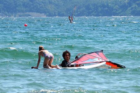 Varna, Bulgaria - July, 31,2020: instructors teach the child to ride windsurfing