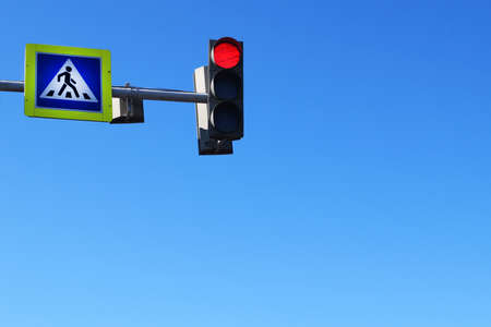 crosswalk sign and red traffic light on blue sky background, copy space. Stock Photo