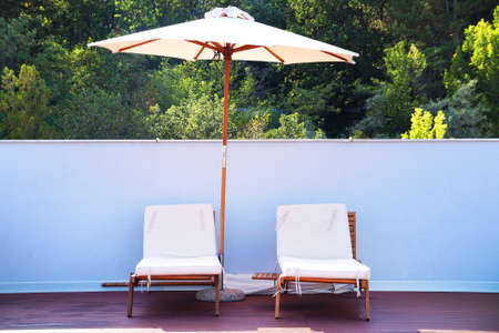two sun loungers under an umbrella on the outdoor patio.