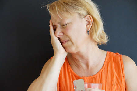 unhappy woman holding her head with her hand, portrait on black background.