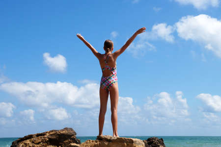 teenager stands in raised hands on a stone by the sea, copy space