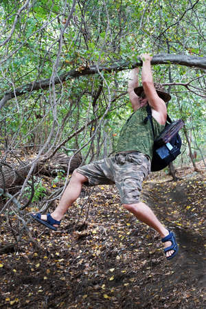 a man with a backpack climbs over a ravine hanging on his hands on a tree.