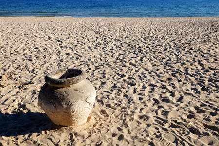 ancient clay pot on the sandy seashore close up 版權商用圖片