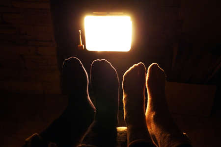 two pairs of feet warming themselves near a burning fireplace.