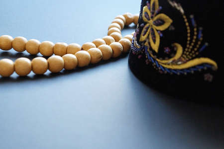 wooden rosary for prayer and embroidered skullcap on dark background. Stock Photo
