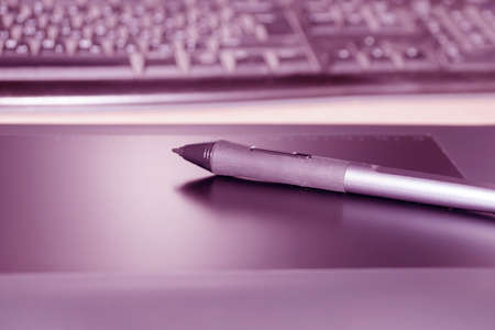 the stylus lies on the graphics tablet against the background of the keyboard.