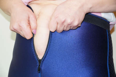 woman puts on neoprene slimming pants close-up.