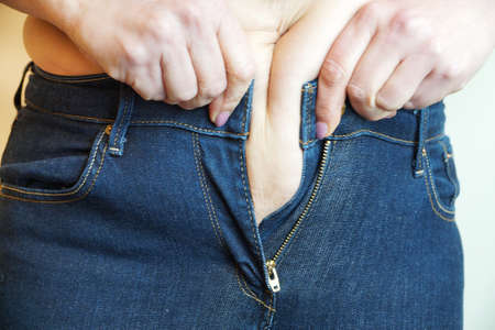 woman with fat belly trying to button up jeans at the waist close-up