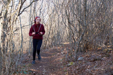 teenage girl in headphones runs along a forest trail with a backpack.