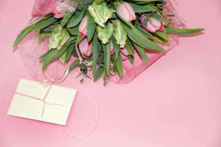 a bouquet of tulips and a gift envelope on a pink background, copy space