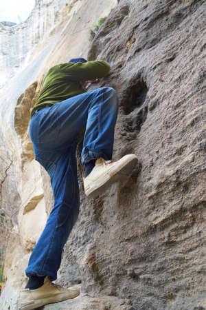 a man in jeans climbing a cliff close-up Standard-Bild
