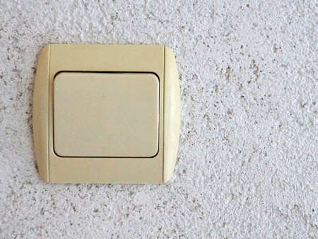 electrical switch on gray plastered wall copy space