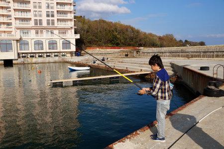 Varna, Bulgaria - November, 15, 2020: japanese boy fishing on the sea pier