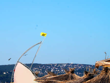 yellow warning flag on a rescue tower on the sea beach.