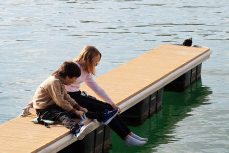 Varna, Bulgaria - November, 15, 2020: children sitting on the pier look at the water in surprise Editorial