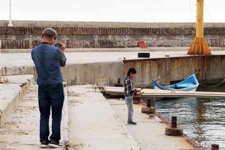 Varna, Bulgaria - November, 15, 2020: father photographs son fishing on the pier