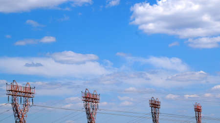 electric towers against the background of a clear sky with white clouds, copy space