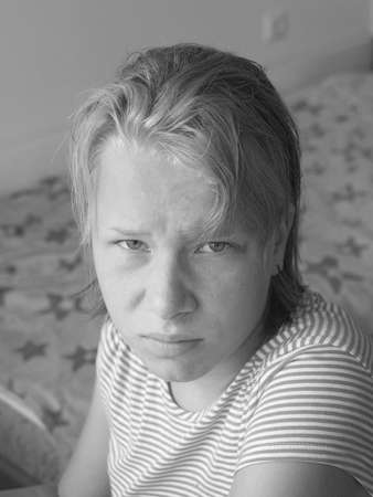 black and white portrait of a teenage girl with a disgruntled expression on her face. Standard-Bild