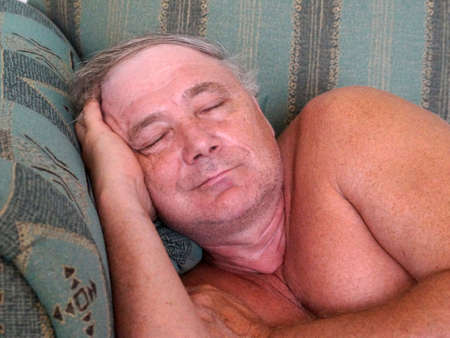 smiling sleeping adult man on sofa close-up