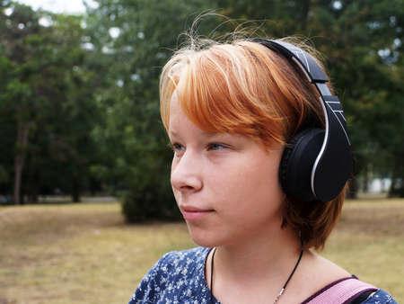 portrait of smiling teenage girl in headphones in the park.