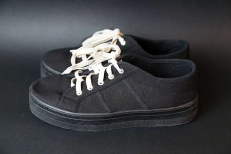 black sneaker with white laces on a black background. Standard-Bild