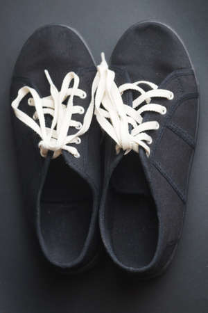 black sneaker with white laces on a black background, view from above Standard-Bild