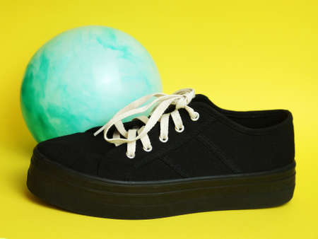 black sneaker with white laces and a blue ball on a yellow background.