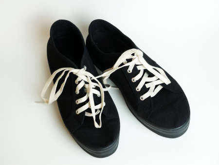 black sneakers with white laces on a white background. Standard-Bild