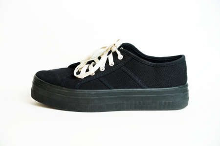 black sneaker with white laces on a white background.