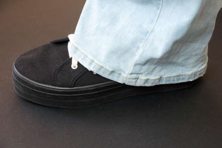 leg of a teenager in black sneakers and blue flared jeans on a white background.