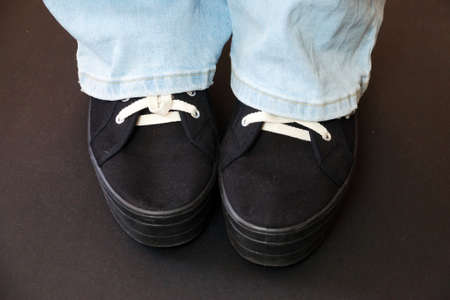 female legs in blue jeans and black sneakers on a black background.