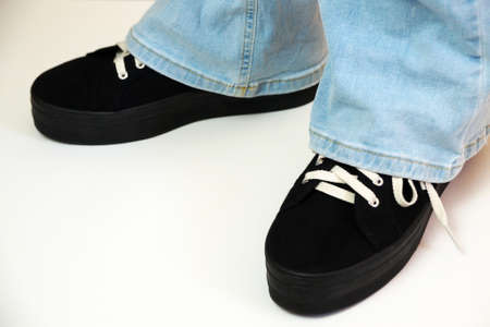 legs of a teenager in black sneakers and blue flared jeans on a white background.