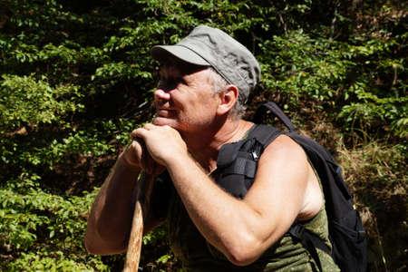 adult smiling man leaning on a stick surveys the surroundings. Standard-Bild