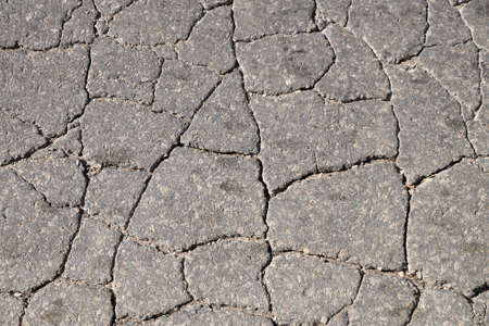 texture of cracked old asphalt for gray background close-up