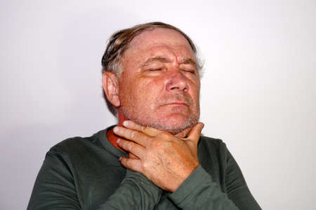 middle-aged man holds his sore throat with his hands, portrait of a sick man. Standard-Bild