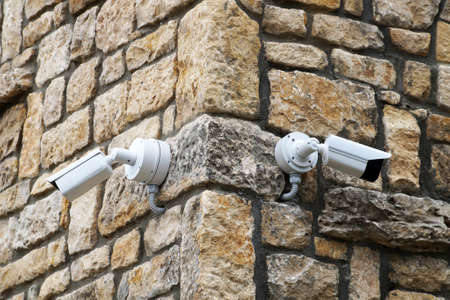 two outdoor surveillance cameras on the corner of an old brick building close-up
