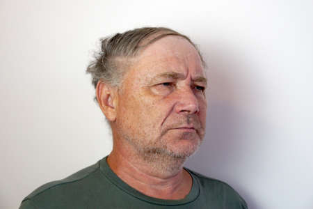 portrait of a disgruntled elderly frowning man on a light background.