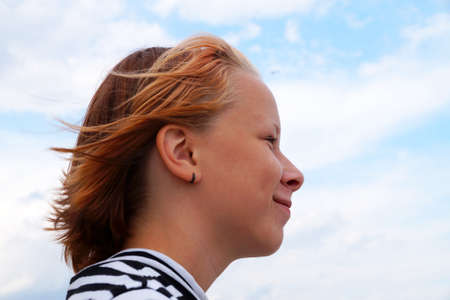 profile of smiling teenage girl with fluttering red hair against blue sky.