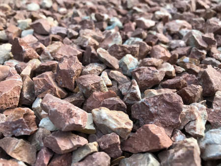 Pink gravel and pebbles, background pattern, small and large sand. Full frame side view