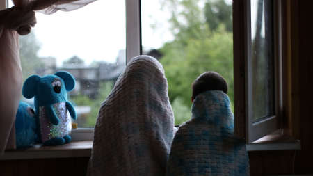two children hiding in soft home blankets look at summer rain through an open window from a dark room