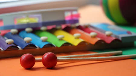 multicolored metal xylophone with wooden sticks located on a blurred background of other colored children's toys, a rubber ball and a plastic tambourine
