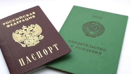 """document """"Russian Federation Passport"""" lying on a document with the inscription """"USSR Birth certificate"""" on a white background as symbols of the transformation of one country into another"""